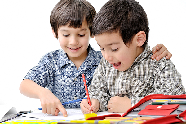 photo of little boy helping friend with writing
