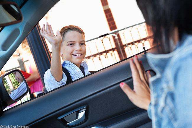 boy waving good bye to mom at school