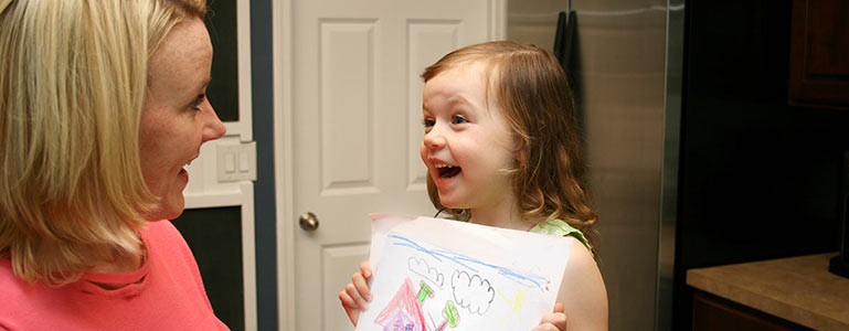 child showing parent her artwork