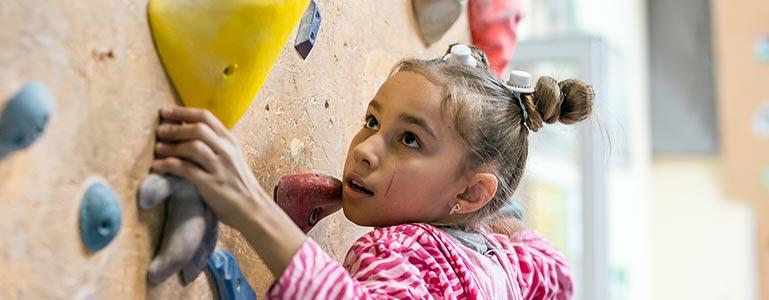 young girl climbing wall