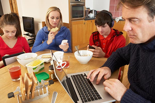 family all giving attention to devices