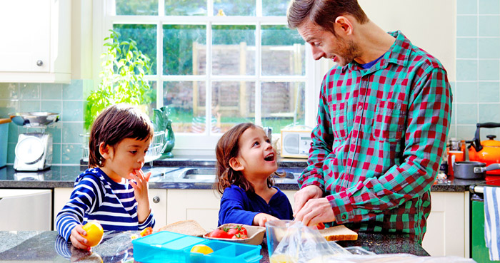 Dad and kids making lunch for school